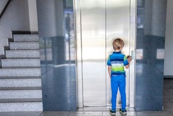 Little boy is calling the elevator next to staircase