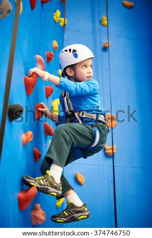 Little boy is climbing to amusement park on blue wall #374746750