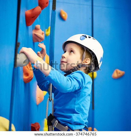 Little boy is climbing to amusement park on blue wall #374746765