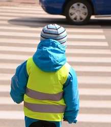 Little boy is crossing zebra crossing where any reckless driver of car pulled into. Child is wearing yellow reflective vest and jacket with reflective strips because of safety.