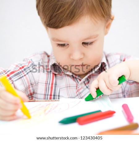 Little boy is drawing on white paper using crayon - stock photo