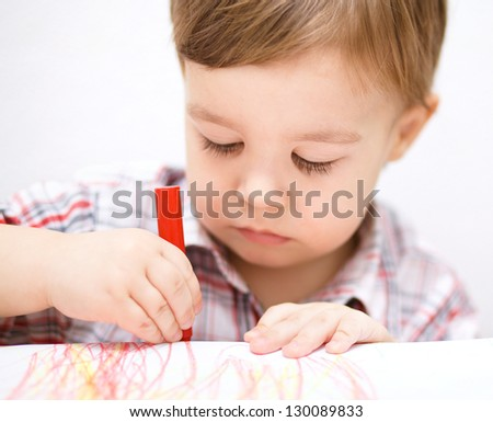Little boy is drawing on white paper using crayon
