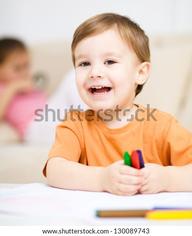 Little boy is drawing on white paper using crayon, his sister sits behind him - stock photo