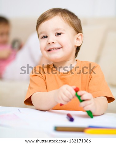 Little boy is drawing on white paper using crayon, his
