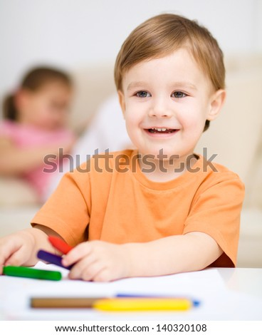 Little boy is drawing on white paper using c