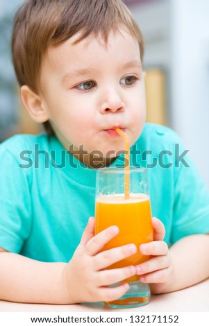 Little boy is drinking orange juice using straw