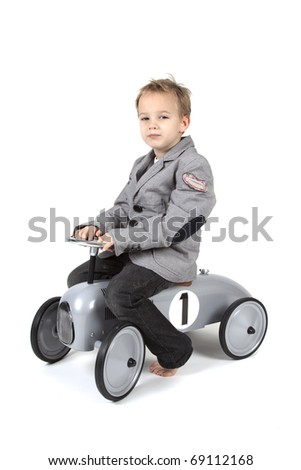 Little boy is driving a toy vehicle