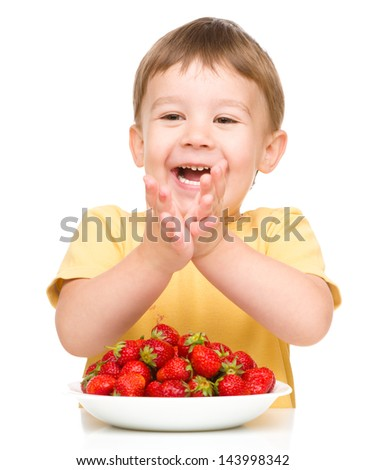 Little boy is eating strawberries and clapping his hands, isolated over white