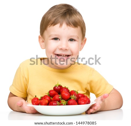 Little boy is eating strawberries, isolated over white