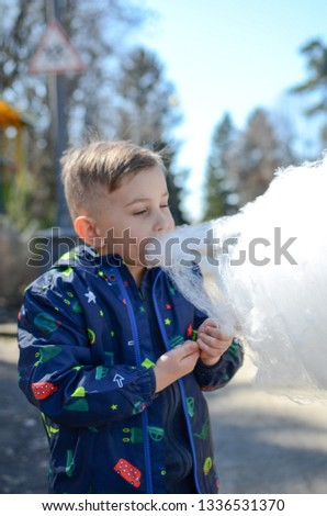 Little boy is enjoying cotton candy. #1336531370