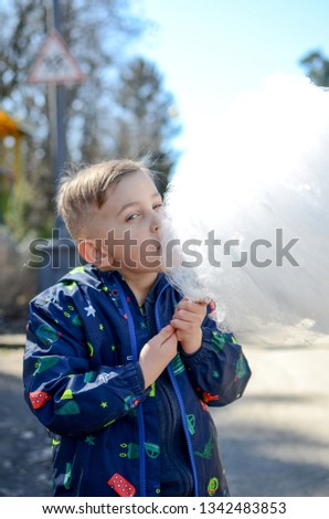 Little boy is enjoying cotton candy. #1342483853