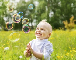 Little boy is happy multi-colored soap bubbles