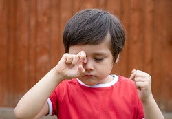 Little boy is having allergy rubbing his eye, Kid scratching his eyes while playing outdoor in summer, Child having allergy itchy face and sneezing while playing outdoor.