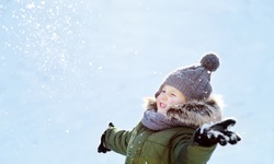 Little boy is having fun playing with snow. Kid dressed in a warm clothes, hat, hand gloves and scarf. Active outdoors leisure with children in winter.