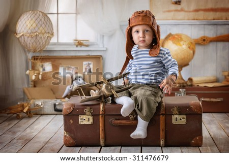 Little boy is himself an aviator and plays with the airplane sitting on a suitcase