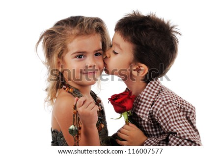 Little boy is  kissing a little girl and they are holding red rose between them. The picture is isolated on white background.