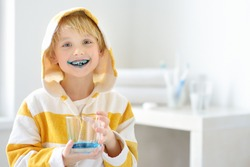 Little boy is learning carefully brush teeth. Child using liquid for disclosing plaque. Teaching children proper oral hygiene. Dental medicine and healthcare for kids.