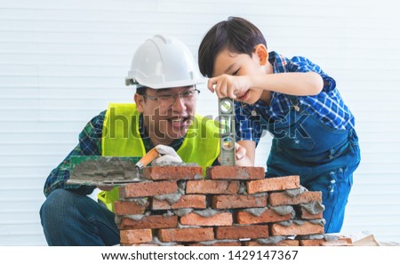 Little boy is learning how to lay down brick work from his builder father. Daddy and His son having a good time making construction block wall together. For Family bonding and togetherness concept.