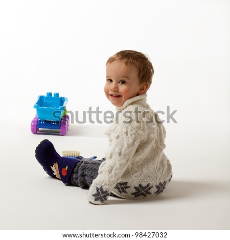 Little boy is looking over shoulder inviting to play - stock photo