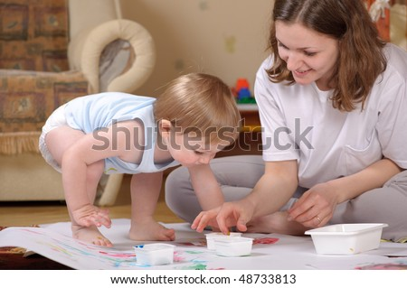 Little boy is painting using his fingers