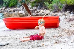 Little boy is playing with bamboo at the seaside on the beach. Toddler sitting on the sand near red rowboat. Child enjoys summer holidays.