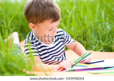 Little boy is playing with pencils outdoors