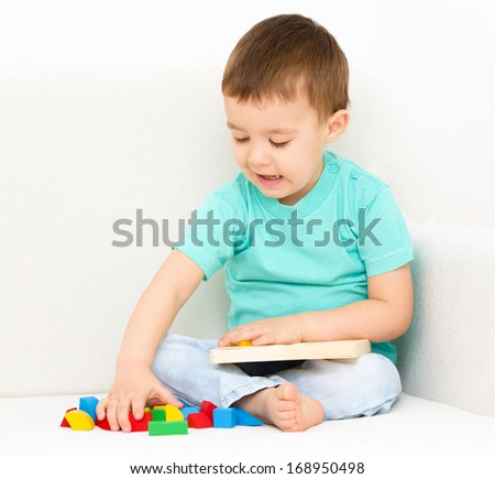 Little boy is playing with puzzle