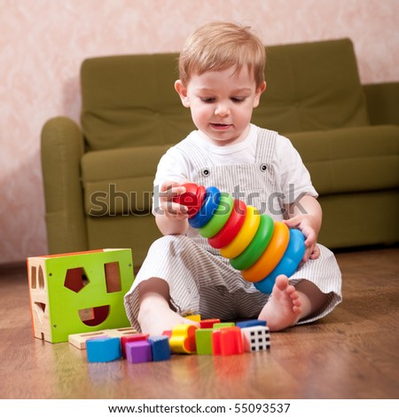Little boy is playing with toy blocks - stock photo