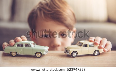 Little boy is playing with toy cars at home