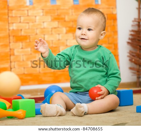 Little boy is playing with toys in preschool while sitting on floor - stock photo