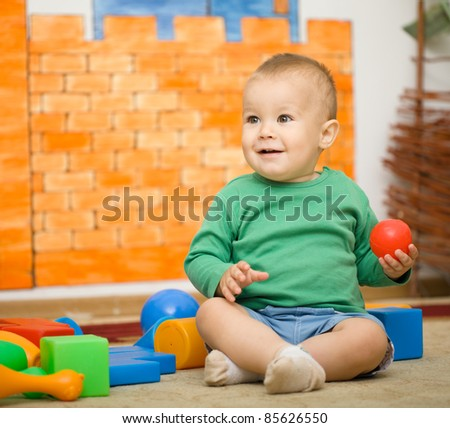 Little boy is playing with toys in preschool while sitting on floor