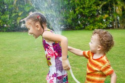 little boy is pouring a water from a hose at her sister