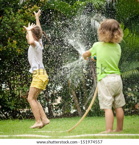 little boy is pouring a water from a hose at his sister