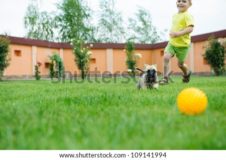 Little boy is racing with his dog to retrieve a ball