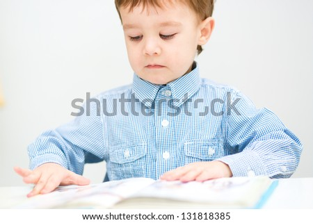 Little boy is reading book, indoor shoot