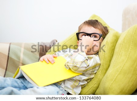 Little boy is reading book while laying on couch, indoor shoot
