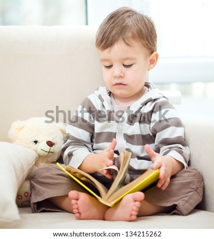 Little boy is reading book while sitting on couch, indoor shoot - st