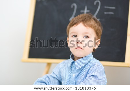 Little boy is sitting on math lesson in preschool