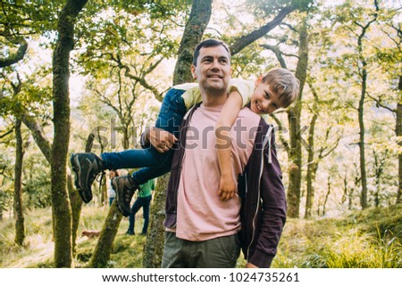 Little boy is smiling at the camera as he is being fireman carried by his father through the woodlands.  #1024735261