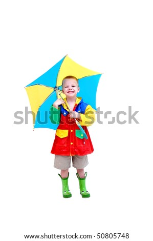 Little boy is wearing a raincoat, rubber boots and holding a brightly colored umbrella.  He has a funny expression on his face as if he is laughing at himself for thinking it might rain.