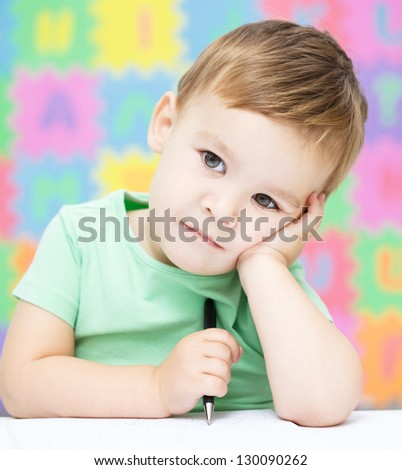 Little boy is writing on his copybook in preschool - stock photo