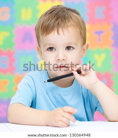 Little boy is writing on his copybook in preschool