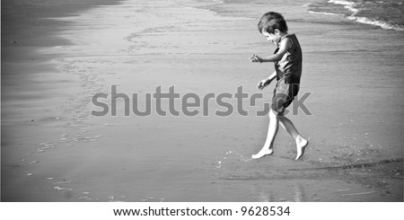 little boy jumping and splashing on the beach, black and white