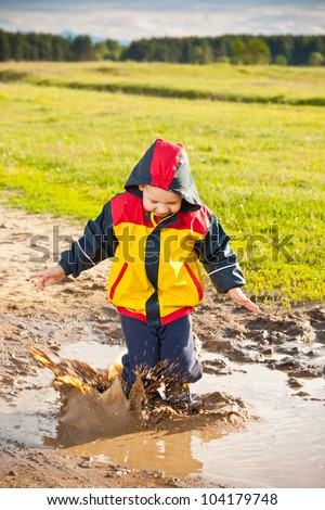 Little boy jumping in a mud puddle.