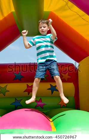 little boy jumping on a bouncy castle