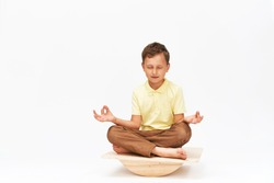 little boy keeps his balance on a special simulator for training muscles. child is engaged on the balance beam, intermediate internal balance. Training of child's brain, development of the cerebellum.