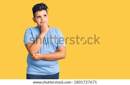 Little boy kid wearing sports workout clothes with hand on chin thinking about question, pensive expression. smiling with thoughtful face. doubt concept.  Photo stock ©