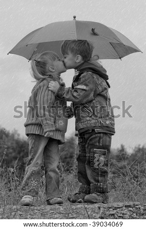 Little boy kiss girl, under umbrella in autumn day