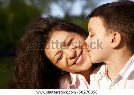 little boy kiss his mother outdoor