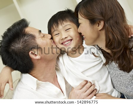 little boy kissed by mother and father.